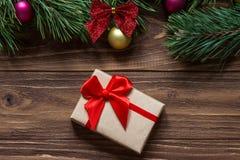 Macro agradable de la caja de regalo de la Navidad en el fondo de madera con las ramas de árbol de pino en el top de la pantalla Foto de archivo