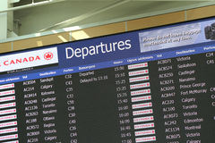 Macro airport departures monitor showing flight gate Royalty Free Stock Images