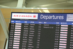 Macro airport departures monitor showing flight gate Stock Image