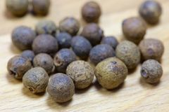 Macro allspice on wooden background.  royalty free stock images