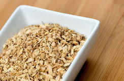 Macro of astragalus root chips against a wood Royalty Free Stock Image