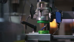 Macro Automated Machine Turns Cap to Bottle with Motor Oil. Macro camera shows automated steel machine tool turning fast green cap to bottle with motor oil stock video footage