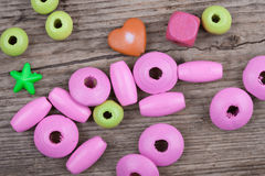 Macro backdrop of little toy beads on wooden background Stock Photo