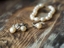 Macro of beautiful pearl earrings and Bride ring on wooden background. Stock Photos