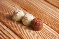 Macro Bianco e caramelle del cioccolato al latte su un fondo di legno leggero Immagini Stock