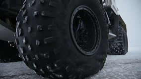Macro Big Black Truck Wheel Rotates on Road. Closeup large black truck wheel with special tire rotates on snowbound road at frosty winter Russian night stock video