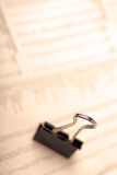 Macro of black paperclip on newspaper. Macro of black paperclip against financial newspaper, warm filter Stock Photography