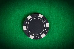 Macro black poker chip on green table Royalty Free Stock Images