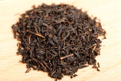 Macro of black tea on wooden board Royalty Free Stock Photos