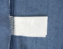 Macro of blank tag on blue jeans background Royalty Free Stock Photos