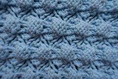 Macro of blue knitted fabric with relief pattern. Macro of light blue knitted fabric with relief pattern stock photo