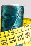 Macro blue spool of thread with measuring tape Stock Photo