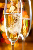 Macro of bubbles of Champagne against sparkling lights Royalty Free Stock Image