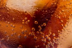 Macro of bubbles and fizz. A cool glass of cola drink with ice.  Royalty Free Stock Photo