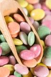 Macro caramelle rotonde variopinte del primo piano con il cucchiaio di legno Fotografia Stock
