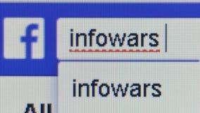Macro cercana para arriba de barra de la búsqueda de Facebook como tipos de usuario el ` de Infowars del ` de la palabra, un siti almacen de video