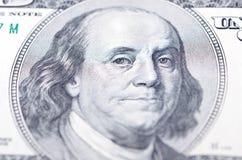 Macro cercana para arriba de la cara de Ben Franklin en la cuenta de dólar de los E Foto de archivo
