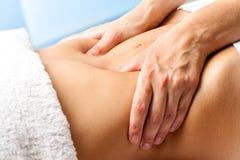 Macro cercana para arriba de las manos que dan masajes al abdomen femenino Imagen de archivo libre de regalías