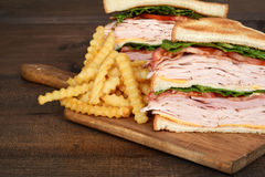 Macro chicken club sandwich with fries. On cutting board stock photos