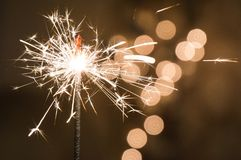 Burning sparkler stands in a glass. Dark background with defocused multi-colored lights of garland. royalty free stock image