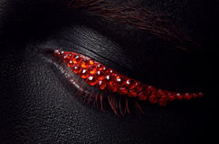 Macro and close-up creative make-up theme: beautiful female eye with black skin and red diamonds, retouched photo Stock Photography