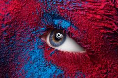 Macro and close-up creative make-up theme: Beautiful female eye with dry paint dust pigment on face, red and blue color Stock Photos