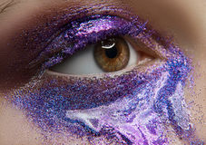 Macro and close-up creative make-up theme: beautiful female eye with purple pigment and sequins, retouched photo Royalty Free Stock Photo