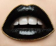Macro and close-up creative make-up theme: beautiful female lips with black lipstick and a gold chain along the contour Royalty Free Stock Images