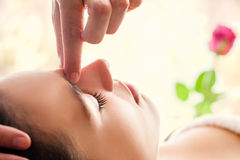 Macro close up of facial relaxing  massage. Macro close up of  relaxing facial massage. Therapist applying pressure with fingers between eyes Stock Image