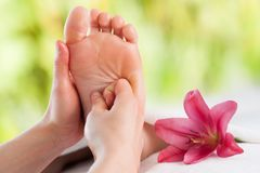 Hands doing foot reflexology. Stock Photos