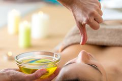 Aromatic oil dripping from finger at Ayurvedic massage. Macro close up of hand with oil drop above woman's head in spa. Aromatic oil in glass bowl next stock image