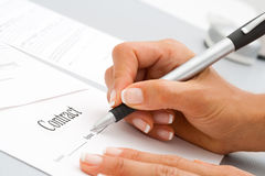 Macro close up of hand signing contract. Royalty Free Stock Images