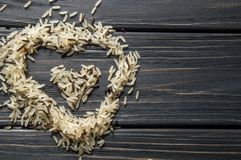 Macro, close up. Heart shaped hill of wild rice on a dark wooden background. Asian cuisine.