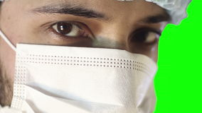 Macro close-up of human eye. A man in a medical mask and cap. stock video footage