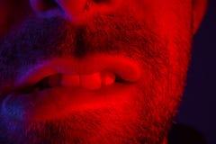 Macro close up on man with seductive facial expression biting hi. S lips. Portrait of flirty young man looking at camera stock image