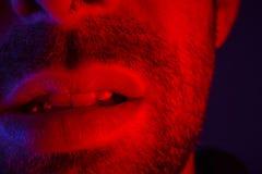Macro close up on man with seductive facial expression biting hi. S lips. Portrait of flirty young man looking at camera royalty free stock photo