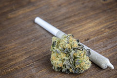 Macro Close Up Of Marijuana Bud With Joint On Wooden Table Stock Image
