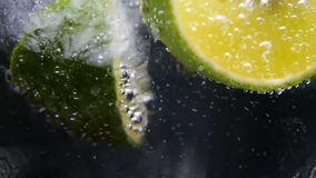 Detox or thirst concept. Healthy, dietary nutrition. Cold lemonade, lime drink. Black background. Macro close-up,refreshing soda tonic fizzy water, lime in Glass stock footage