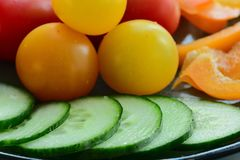 A close-up photo of some fresh vegetables capsicum, tomato and cucumbers, an excellent healthy snack or a side dish. Macro; close-up; structure and colour of royalty free stock photos