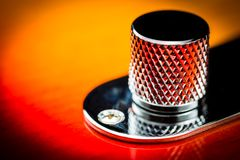 Macro close up of a vintage guitar volume or tone knob. Close up of the front of a vintage electric guitar with a beautiful red to yellow sunburst paint job on stock images
