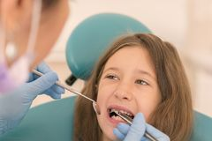 Macro close up of young child with open mouth at dentist. Teeth checkup at dentist& x27;s office. Dentist examining girls teeth in stock photos