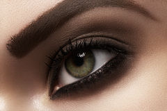 Macro closeup of female eye with fashion makeup, strong eyebrows. Cosmetics and beauty care. Macro close-up of beautiful green female eye with dark fashion smoky stock images