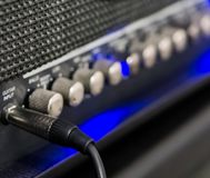 Macro closeup of a guitar cable plugged into the amplifier, professional music equipment stock photos