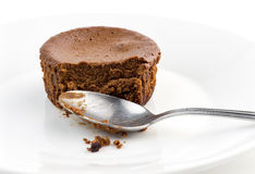 Macro closeup of half eaten chocolate cake muffin with spoon Royalty Free Stock Images