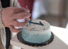 Closeup of woman placing candle on birthday cake with number one stock images