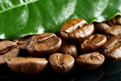 Macro closeup shot of coffee with green leaf on black Royalty Free Stock Photos