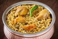 Chicken biryani closeup. Macro closeup view of delicious Indian chicken biryani served in authentic copper utensil. Natural light used royalty free stock photography