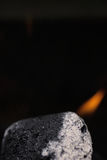 Macro coal. Macro shot of a single charcoal emitting flame royalty free stock photography