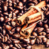 Macro Coffee beans and cinnamon sticks on grunge wooden backgrou Royalty Free Stock Images