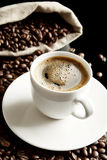 Macro coffee with foam and sack at breakfast on black background Stock Photos